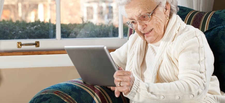 senior woman using ipad in her room