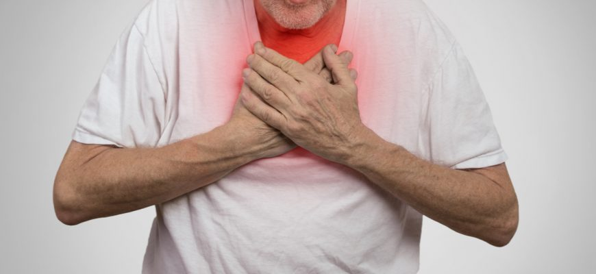 Male senior citizen holds his hands onto his chest in pain.