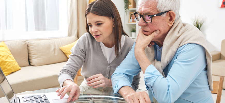 A senior and his daughter view medicare and assisted living costs.