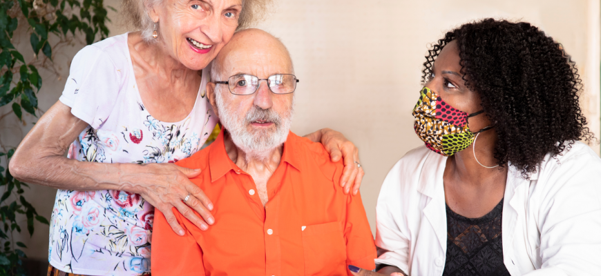 A masked nurse and two residents at an assisted living facility.